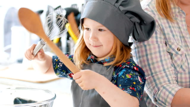 Little girl playing with spoon and whisk in the kitchen video