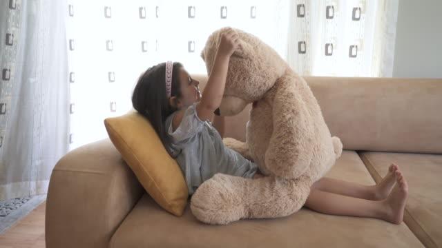 vídeos de stock e filmes b-roll de little girl playing with teddy bear - teddy bear