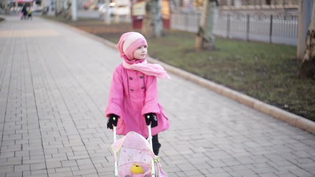 vidéos et rushes de fillette jouant un jouet poussette dans le parc - extérieurs d écoles
