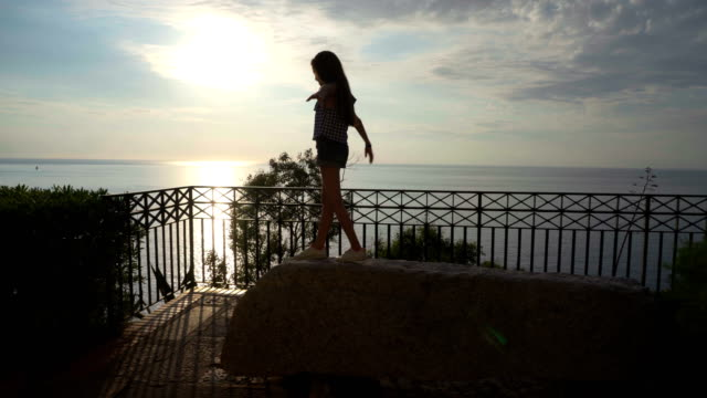 little girl plays at the the sunset on the sea, italy,lookout, calabria , summer,tropea - video di tropea video stock e b–roll