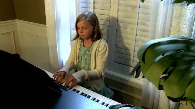Little girl plays piano in blue dress video