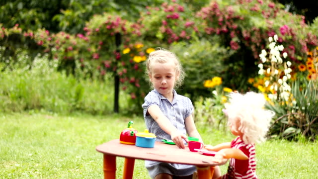 Little girl plays with a doll - Stock video Little girl preschooler playing usual role-play mother with doll in the summer garden. Toy dishes,pretend food, tea parties with a doll at the toys table. doll stock videos & royalty-free footage