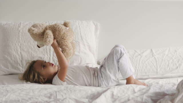 a little girl plays with her stuffed bear and cuddle, kiss and have fun. concept of: tenderness, softness, peaceful dreams. - pillow stock videos & royalty-free footage