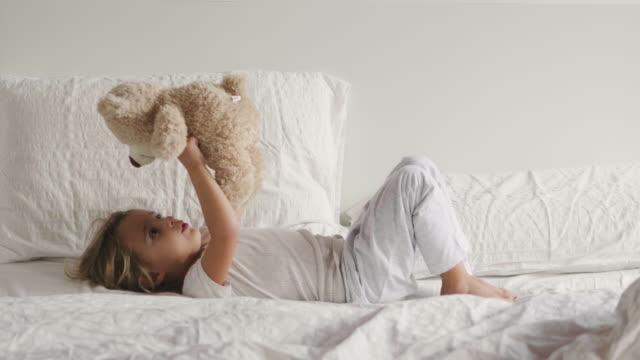 vídeos y material grabado en eventos de stock de una niña juega con su oso de peluche y abrazarse, besar y divertirse. concepto de: ternura, suavidad, sueños pacíficos. - almohada