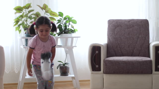 little girl plays with homemade toy horse at home