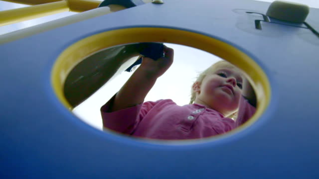 Little girl pokes her head through big circle video