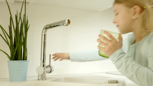 Little Girl Pouring Tap Water HD1080p: Little girl pouring tap water into a glass in the kitchen at home. faucet stock videos & royalty-free footage