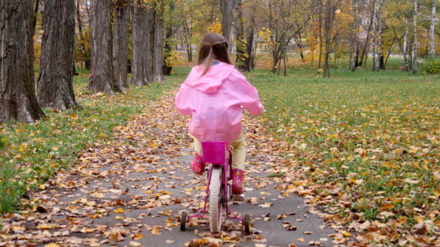 Little girl practice to ride a pink bicycle in the autumn park video