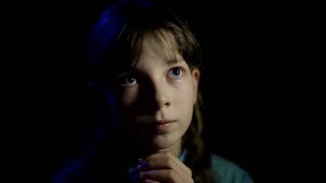 vidéos et rushes de petite fille priant dans une chambre sombre - baptême