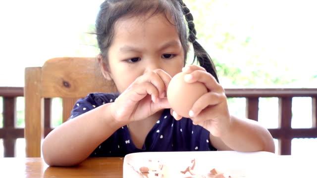 kleines mädchen bereiten eiern zum kochen. konzentrieren sich auf die eiern peeling. - gar gekocht stock-videos und b-roll-filmmaterial