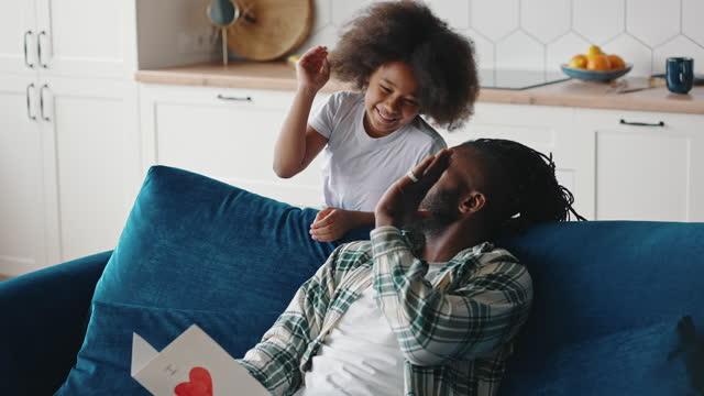 liten flicka presenterar handgjorda gratulationskort till sin pappa, lycklig man njuter av stor gåva och kramar sin dotter - hemmagjord bildbanksvideor och videomaterial från bakom kulisserna