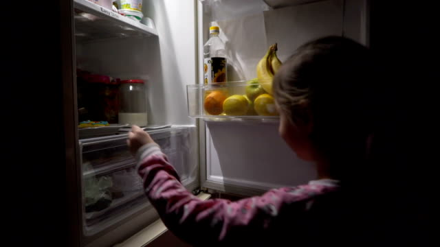 Little girl pulls out cookies from the fridge. Little cute girl opens the refrigerator at night and pulls out a plate of cookies. hungry child stock videos & royalty-free footage