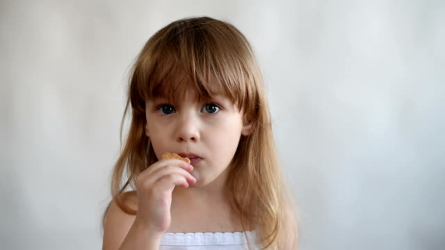 Little girl putting a cookie to her mouth video