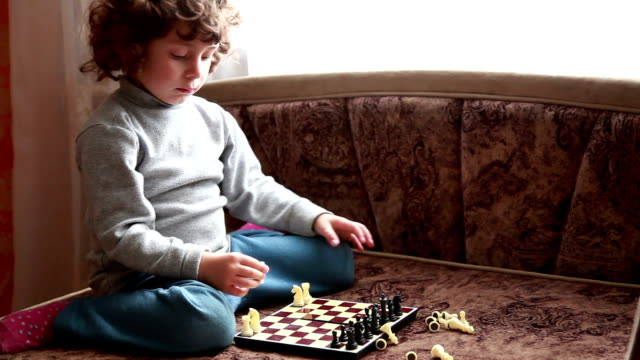Little girl putting chess pieces on the chessboard Close-up of a little girl sitting on the bed and arranging white chess pieces on the board, licking her lips in excitement, side view knight person stock videos & royalty-free footage