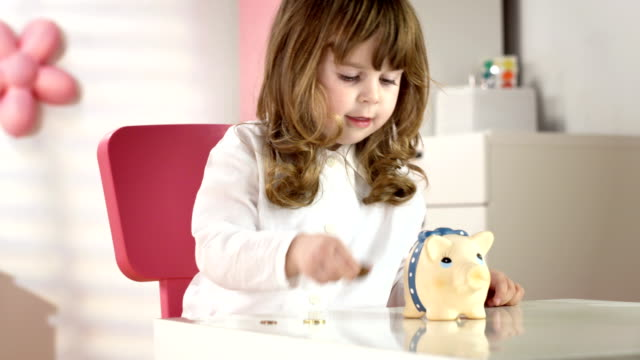 HD DOLLY: Little Girl Putting Coins Into A Piggy Bank video