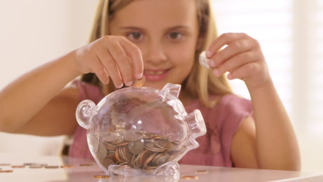 Little girl putting coins into piggy bank. Little girl putting coins into piggy bank. piggy bank stock videos & royalty-free footage