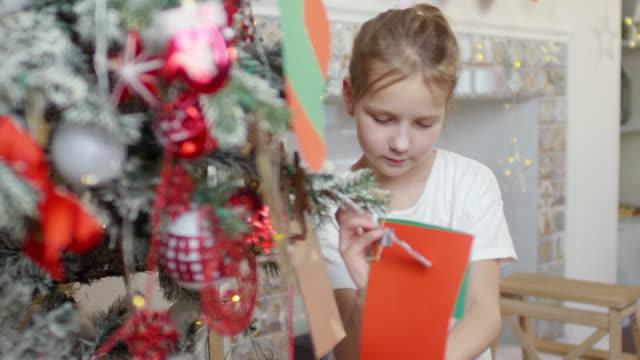 kleines mädchen putting dekorationen auf weihnachtsbaum zu hause - weihnachtsstrumpf stock-videos und b-roll-filmmaterial