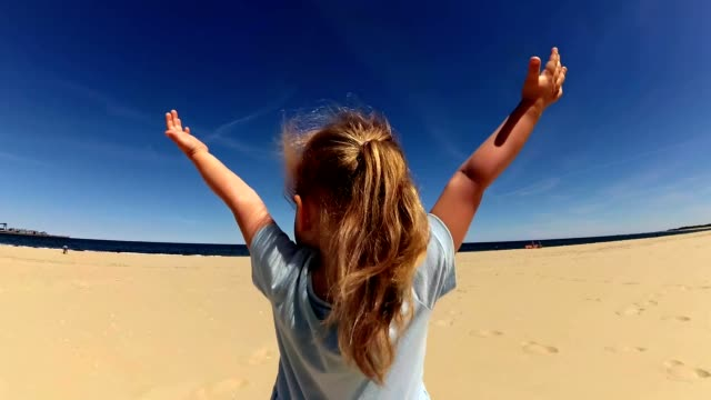 Little Girl Reaching The Sky Hands Praying Smiling on Sunny Beach video