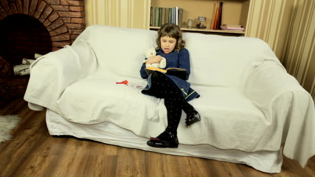 Little girl reading a book aloud teddy bear in the living room on the couch video