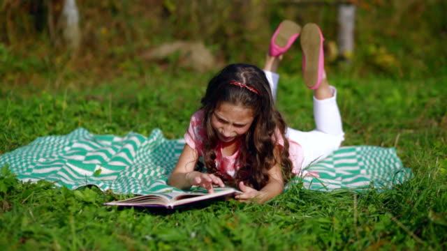 Little girl reading a book in the garden video