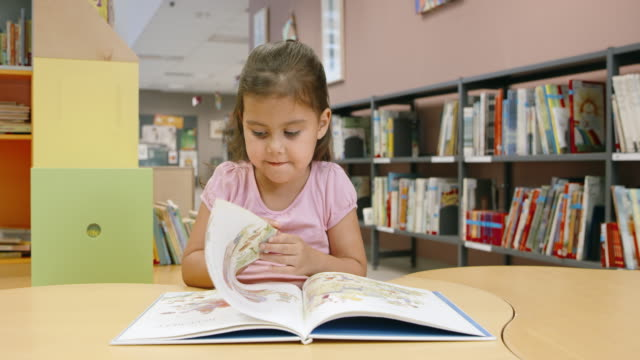 DS Little girl reading at the children's table in a public library video