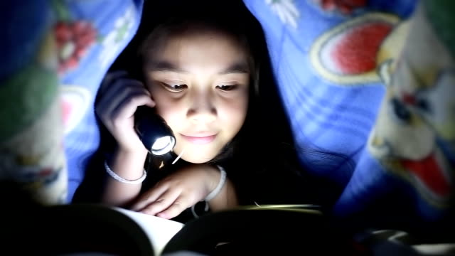 Little girl reading book under the blanket HD 1080P : Little girl reading book under the blanket with flashlight in her hand. flashlight stock videos & royalty-free footage