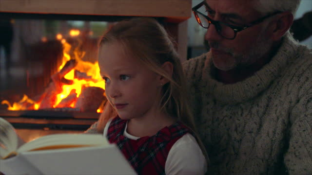 Little girl reading book with grandfather near fireplace Little girl reading book with grandfather near fireplace at home. Senior man with grandaughter reading a book. fireplace stock videos & royalty-free footage