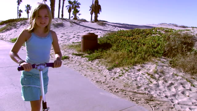 Little girl rides scooter on boardwalk at beach video