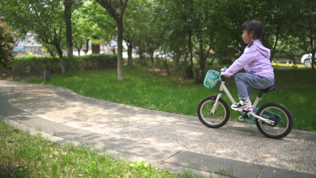 Little girl riding a bicycle Little Chinese girl riding a bicycle. lockdown viewpoint stock videos & royalty-free footage