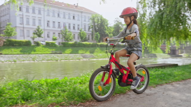Little girl riding a bike in the park followed by her parents on a tandem bike