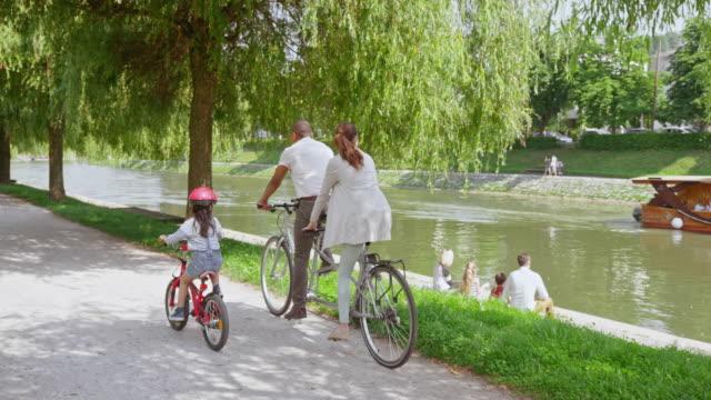 vídeos de stock e filmes b-roll de slo mo cs little girl riding her bike along her parents riding through the park on the tandem bike - green city