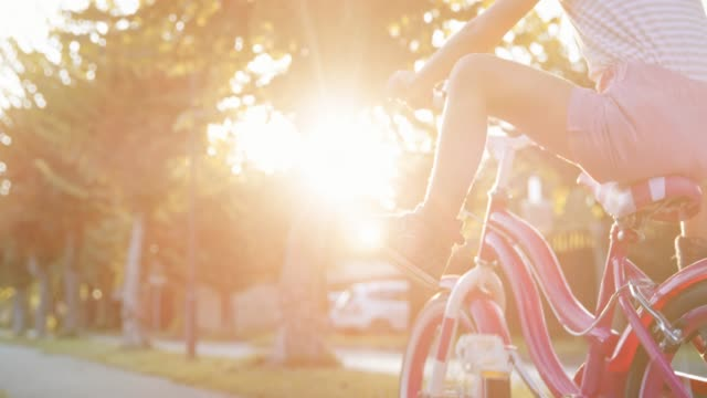 SLO MO Little girl riding her bike, pushing the pedals and then raising her feet in the air