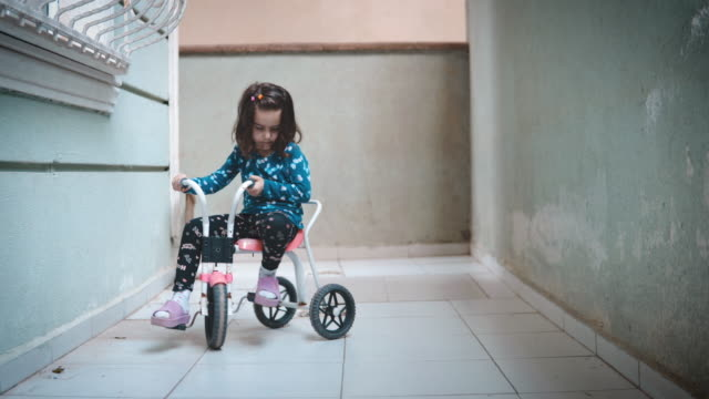 Little girl riding tricycle on balcony. Feeling lonely because she is not allowed to go outside and play.