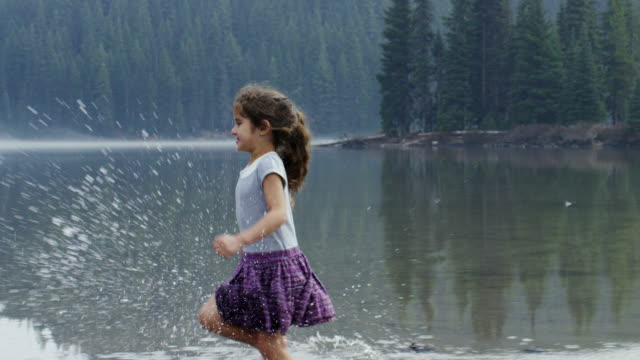 Little girl running and playing in the shallow water. video