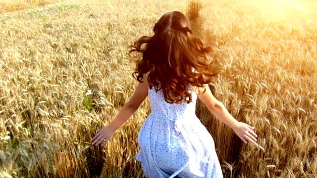 Little girl running cross the wheat field at sunset