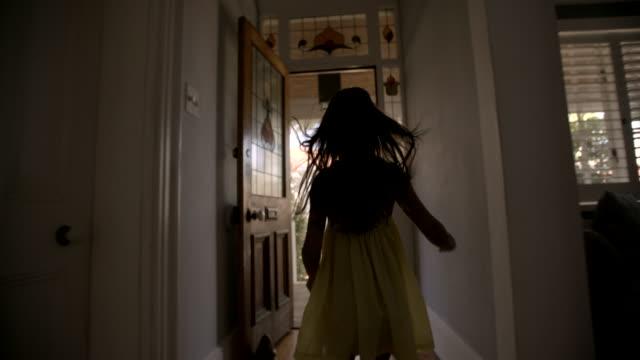 Little girl running happily to an open front door