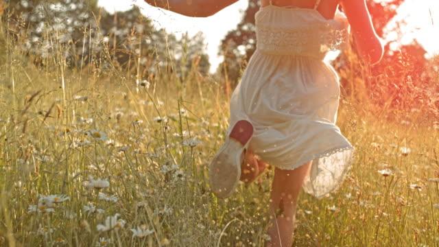 SLO MO TS Little girl running in high grass towards the sun video