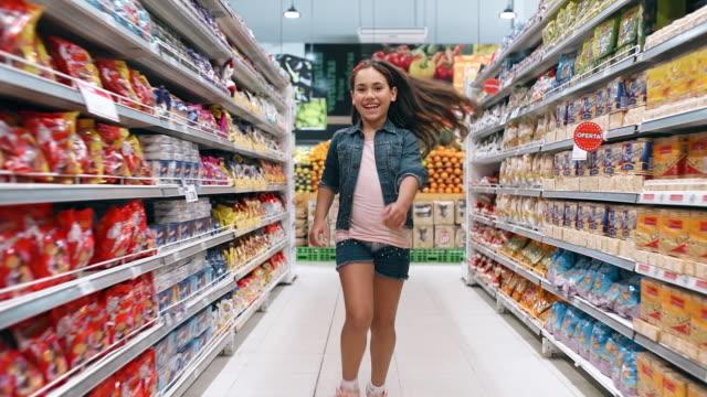 vídeos y material grabado en eventos de stock de niña corriendo pasillos de supermercado - snack aisle