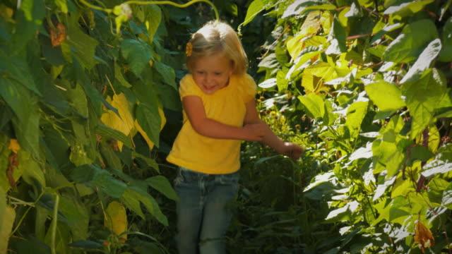 Little girl running through thick vegetation. video