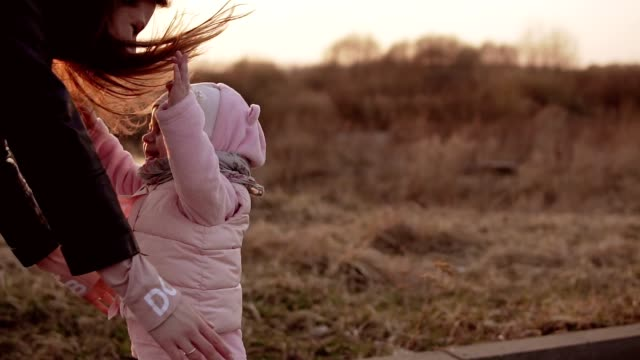 Little girl running to mother and laughing at sunset in slow motion