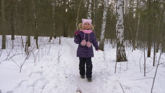 Little girl runs along path in winter forest. Girl overcomes obstacles. Girl with a stick in hand fall rise and walk. video