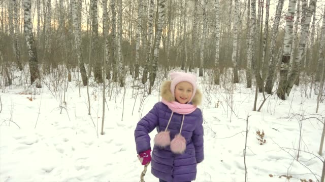 Little girl runs through birch woods with a stick. Young girl happy jokes and falls to snow in winter forest. video