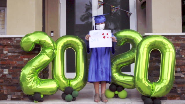 Little girl school graduation in front of her house during lockdown 2020
