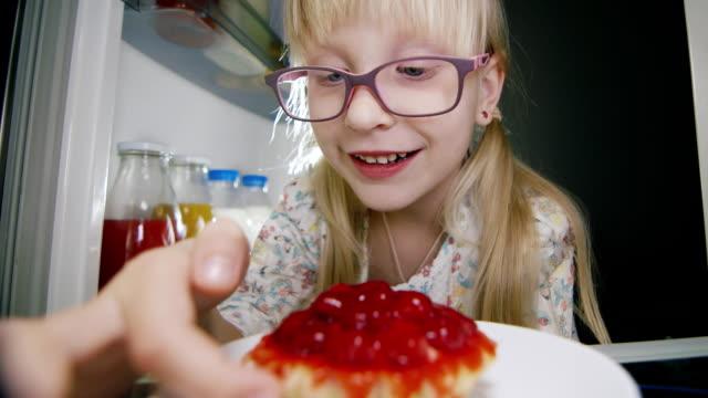 A little girl secretly tastes a strawberry cake inside the refrigerator. Childhood pranks, happy childhood video