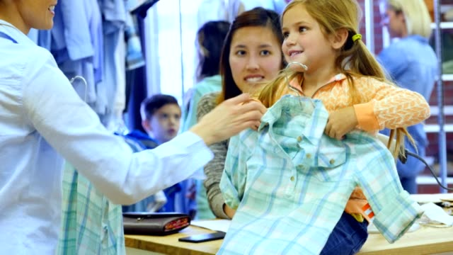 Little girl shops in department store with her mom Beautiful Caucasian little girl shops in a boutique or department store with her mom. Her mom hands her a pastel plaid shirt and girl holds it up to herself and smiles. The salesperson is behind the girl. Shoppers are shopping in the background. department store stock videos & royalty-free footage