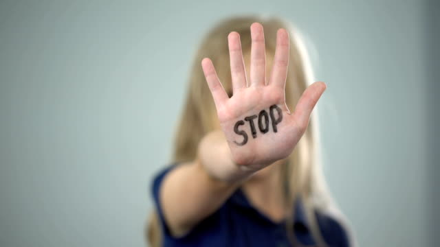 vídeos y material grabado en eventos de stock de niña mostrando la señal de stop, tema de abuso infantil, crueldad en la familia, conciencia - stop sign