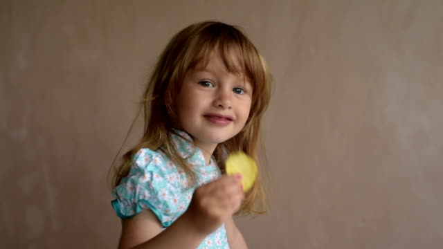 Little girl shows crisp and eats it Little girl shows crisp and eats it. potato chip stock videos & royalty-free footage