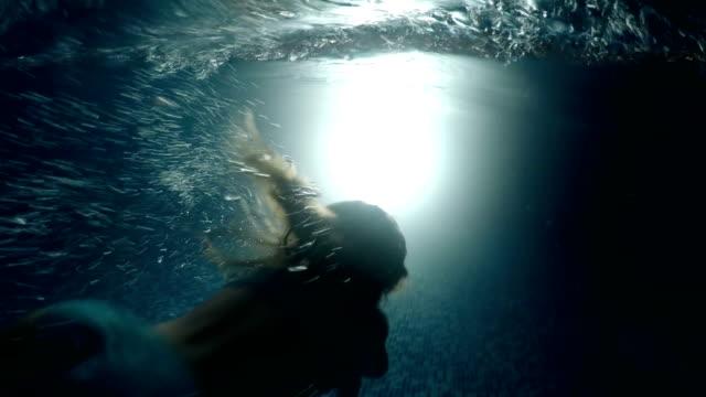 Little girl silhouette swimming underwater toward light in dark pool