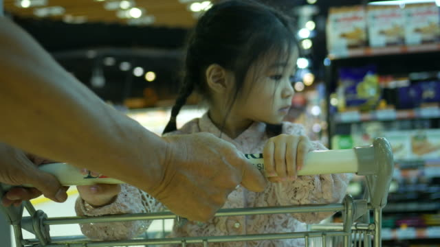 little girl sit on shopping cart while shopping with family video