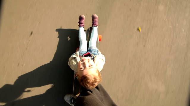 Little girl sits on a longboard, which is run by her dad. POV video